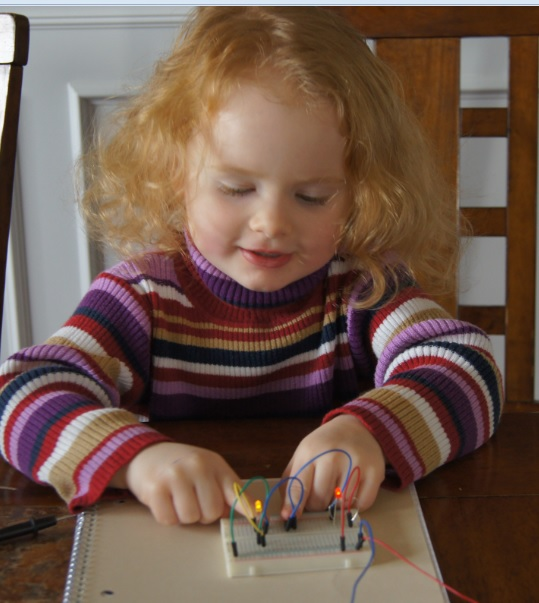 Young student demonstrates pushing buttons A and B on a breadboard to make two lights shine.